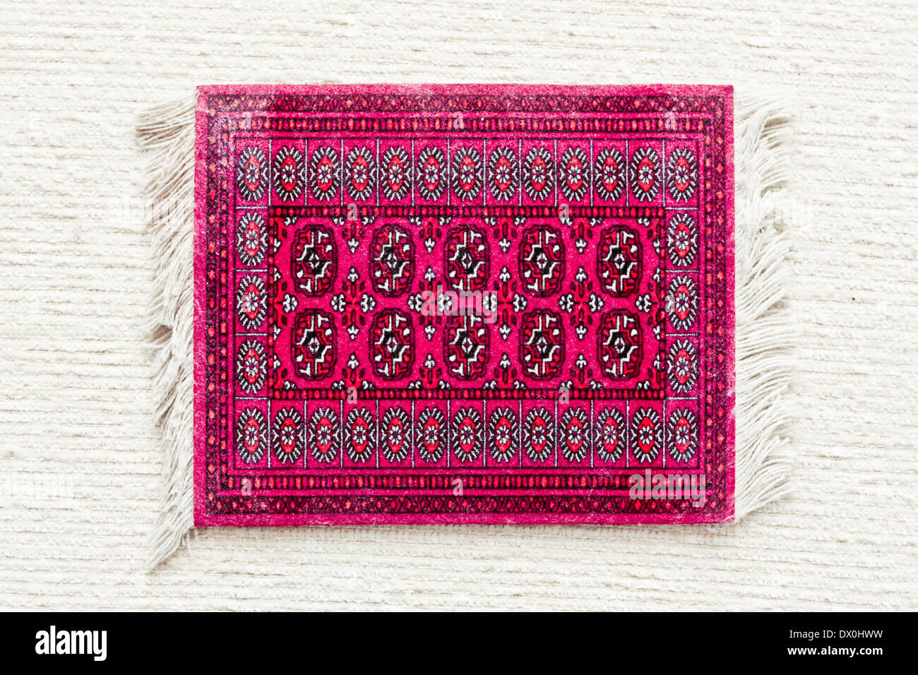A red asian rug on a white cloth surface Stock Photo