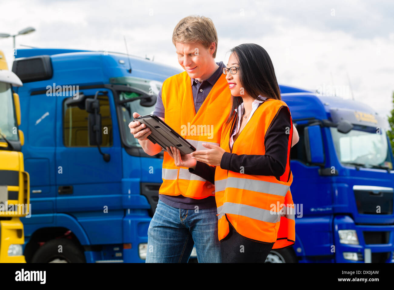 Logistics - proud driver or forwarder and female coworker with tablet computer, in front of trucks and trailers - Stock Image