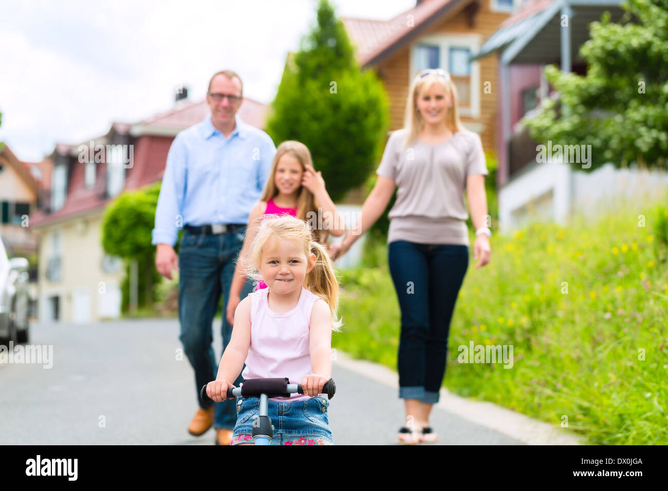 Young family with Mother, father and daughters walking through a housing estate, perhaps they make a trip or excursion Stock Photo