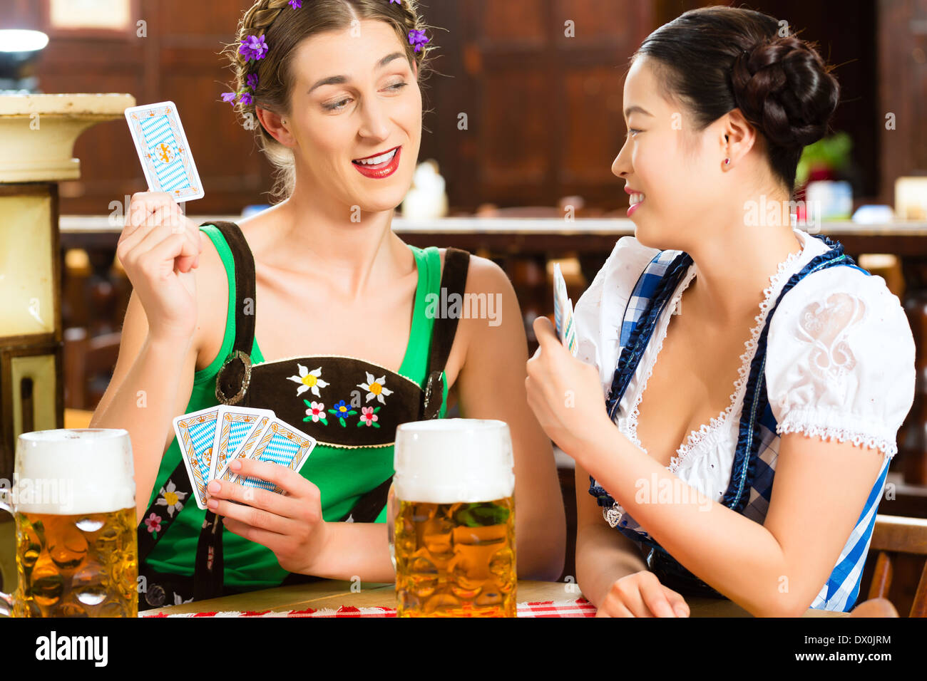 In Pub - friends in Tracht, Dirndl and Lederhosen drinking a fresh beer in Bavaria, Germany playing cards - Stock Image
