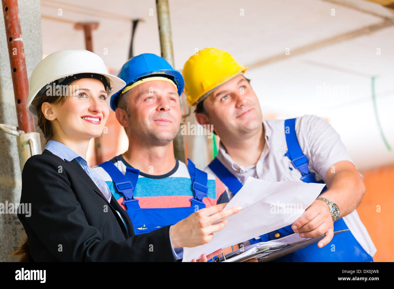 Charming Construction Site Team Or Architect And Builder Or Worker With Helmets  Controlling Or Having Discussion Of Plan Or Blueprint