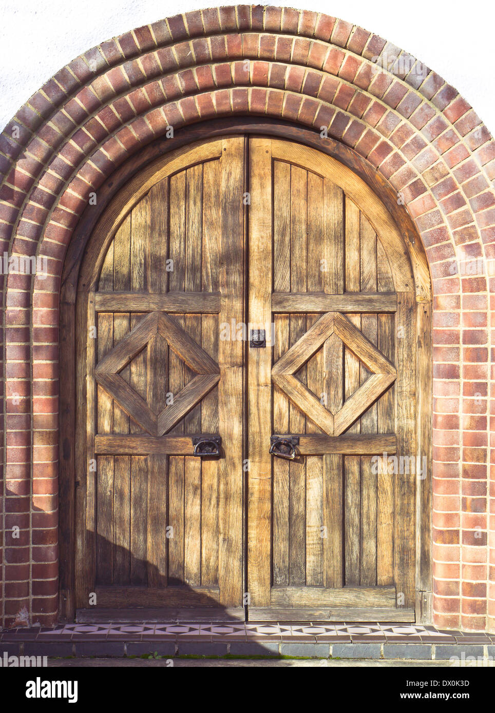 Archway and wooden double doorway in a house in the UK Stock Photo