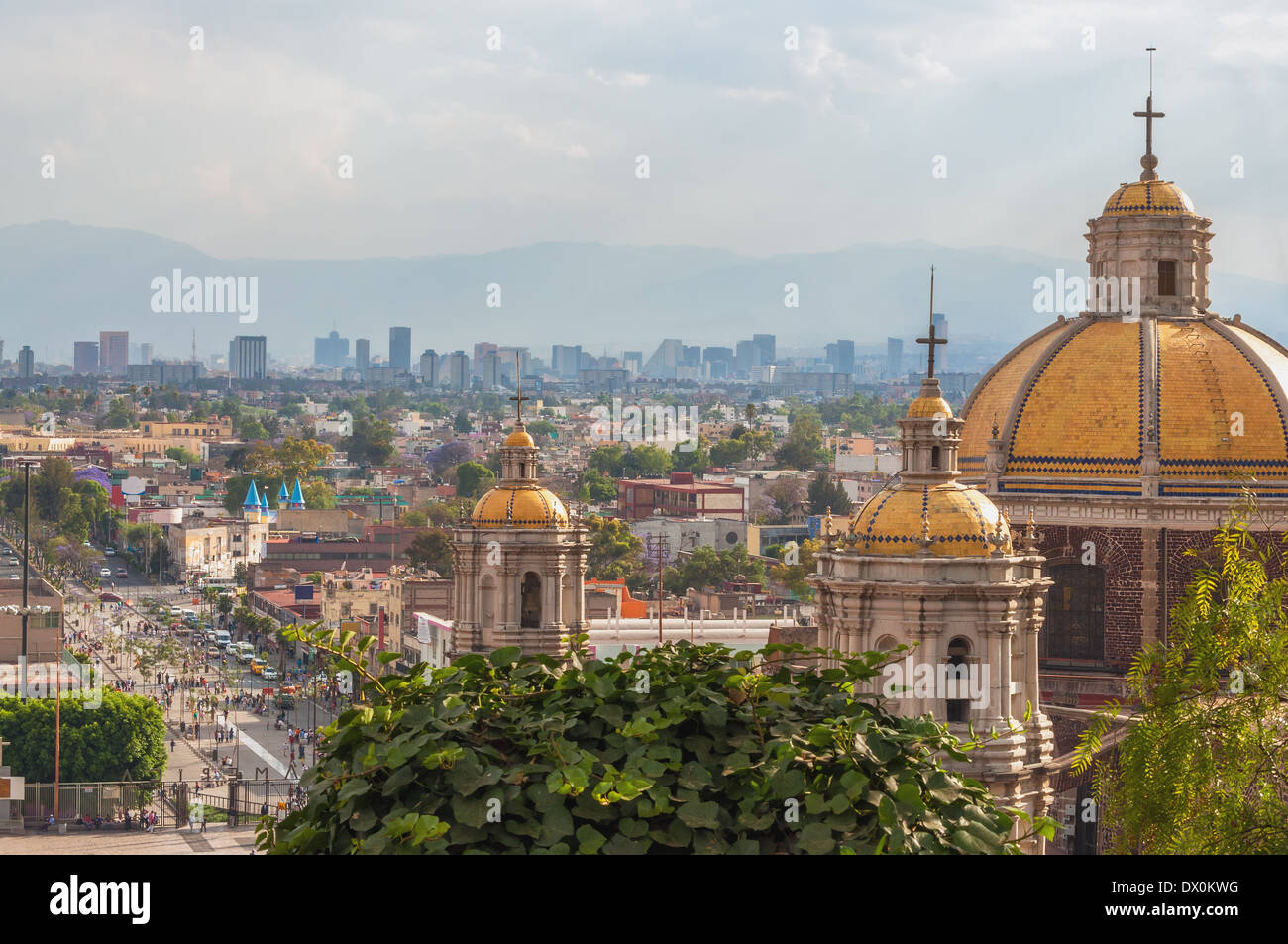 Old Basilica of Guadalupe with Mexico City skyline behind it - Stock Image