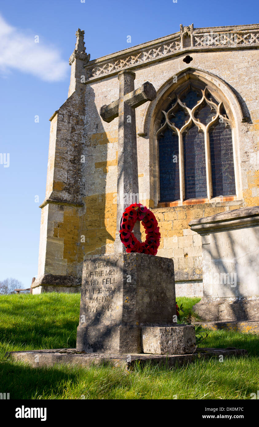 World War memorial and poppy wreath at St Lawrence Church, Bourton on the hill, Cotswolds, Gloucestershire, England - Stock Image