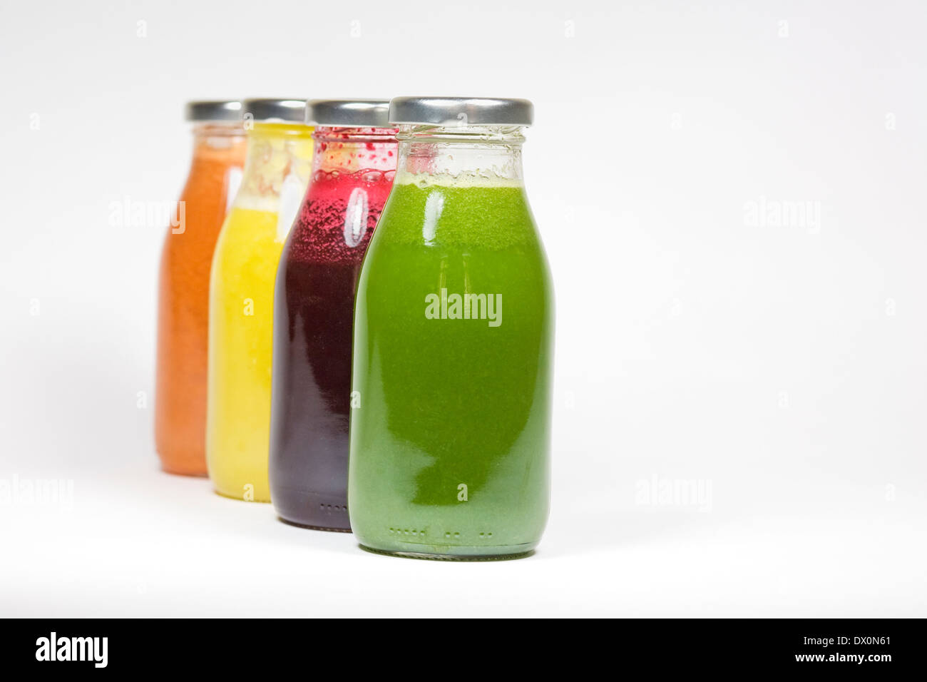 Four freshly squeezed juices in glass bottles. - Stock Image