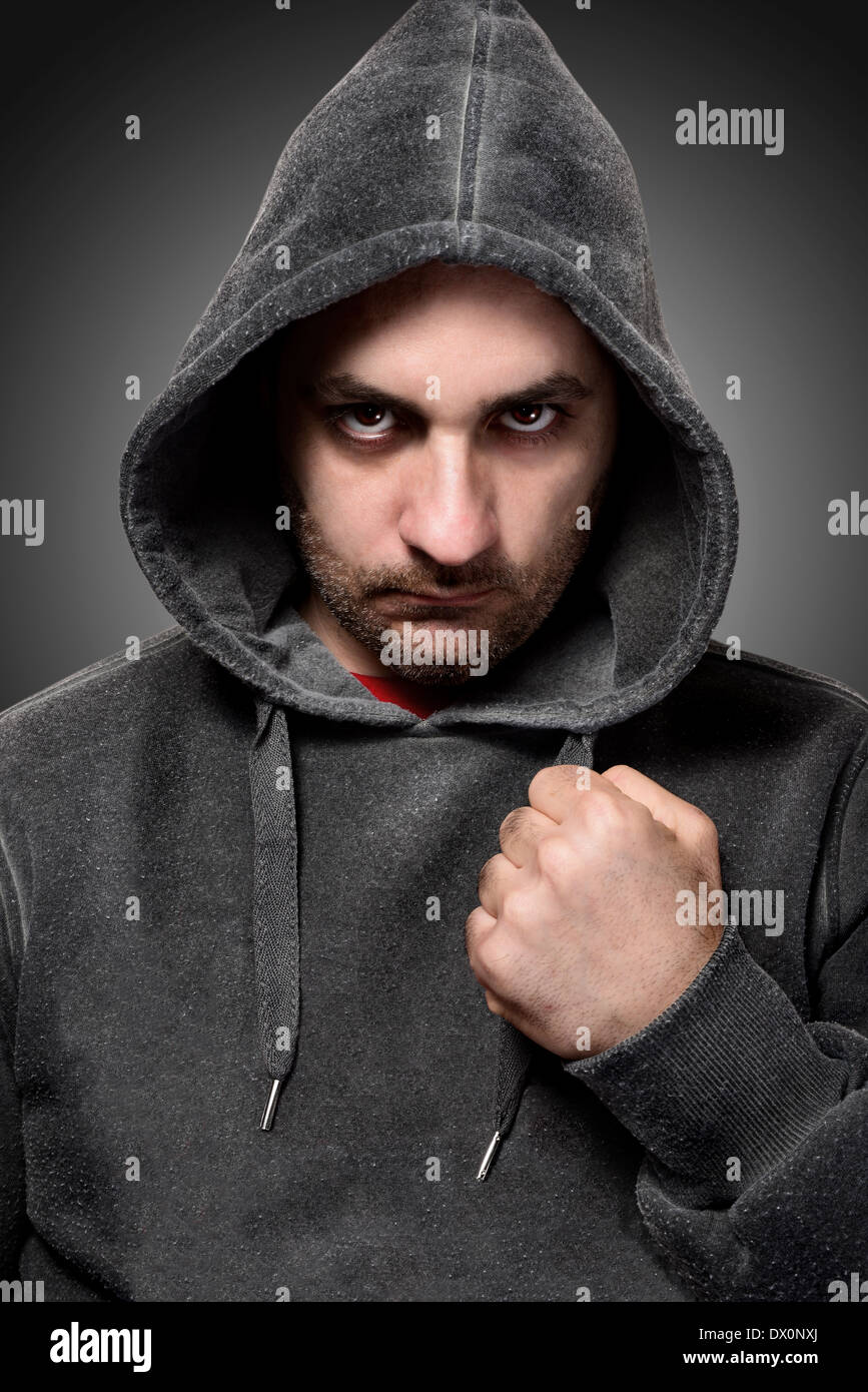 Young angry gangster with the hood on his head - Stock Image