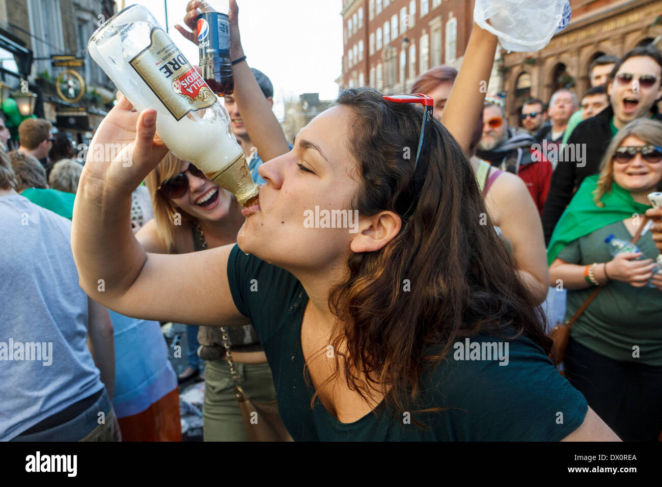 A young woman drinks cider from a bottle as she is encouraged by onlookers during St Patrick's Day Celebrations. London  UK - Stock Image