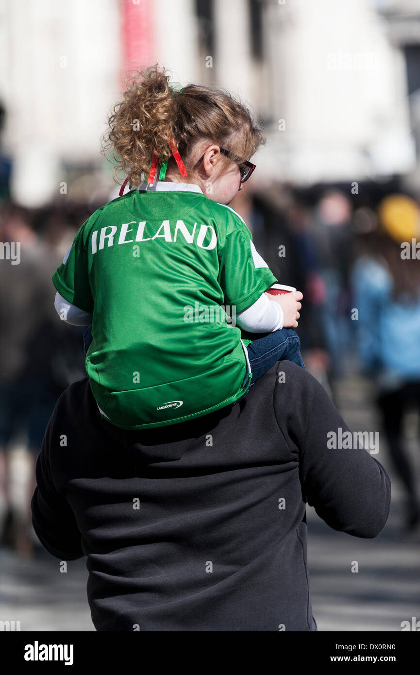 London, UK. 16 March 2014. A young girl wearing an Irish T shirt is carried on her father's shoulders during the annual St Patrick's Day Parade in London.  Photographer:  Gordon Scammell/Alamy Live News - Stock Image