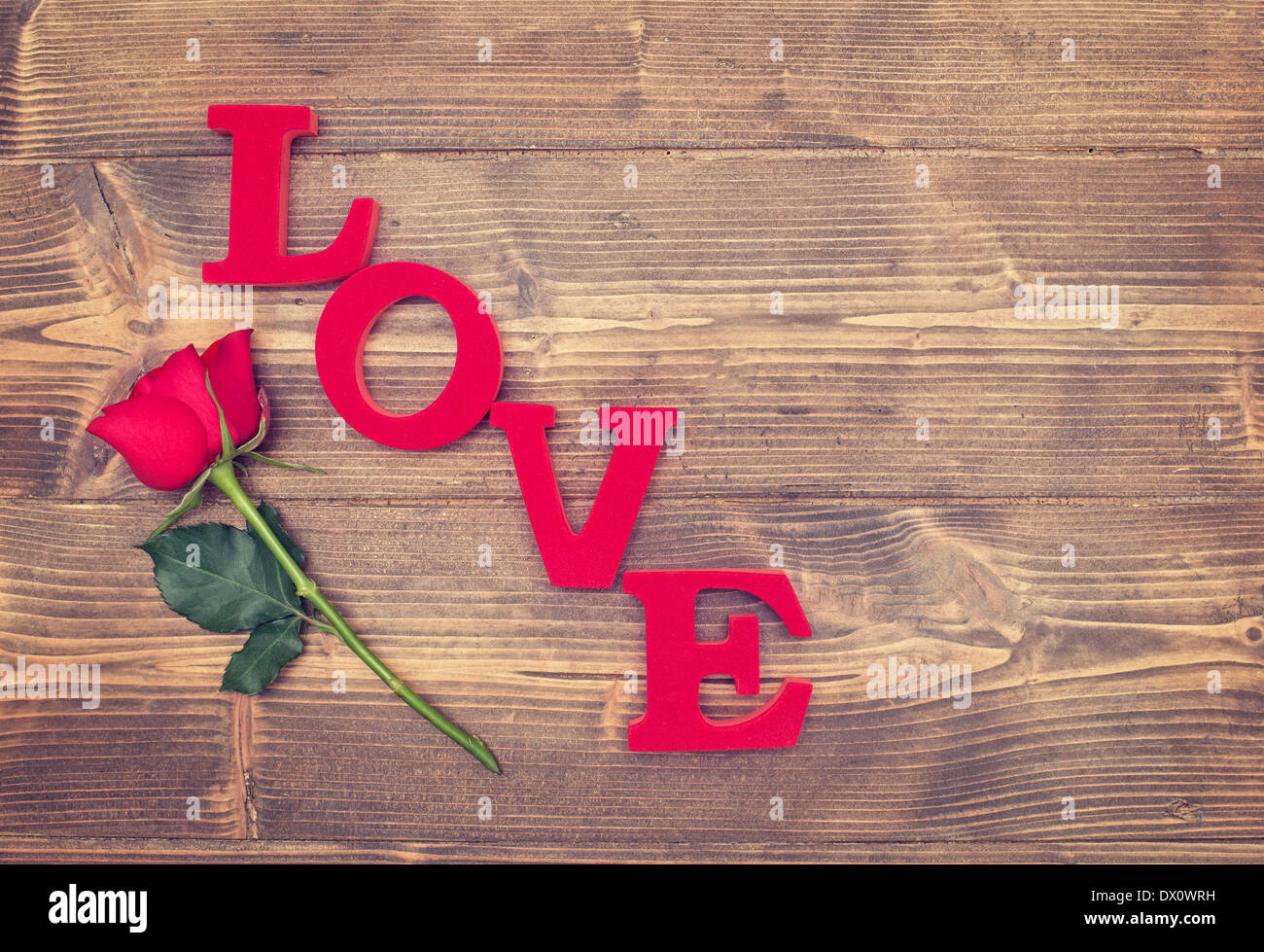 Single Red Rose And The Word Love On A Rustic Background