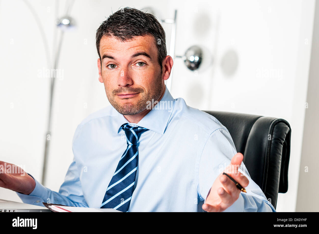 busy man hiding behind a stack of files - Stock Image