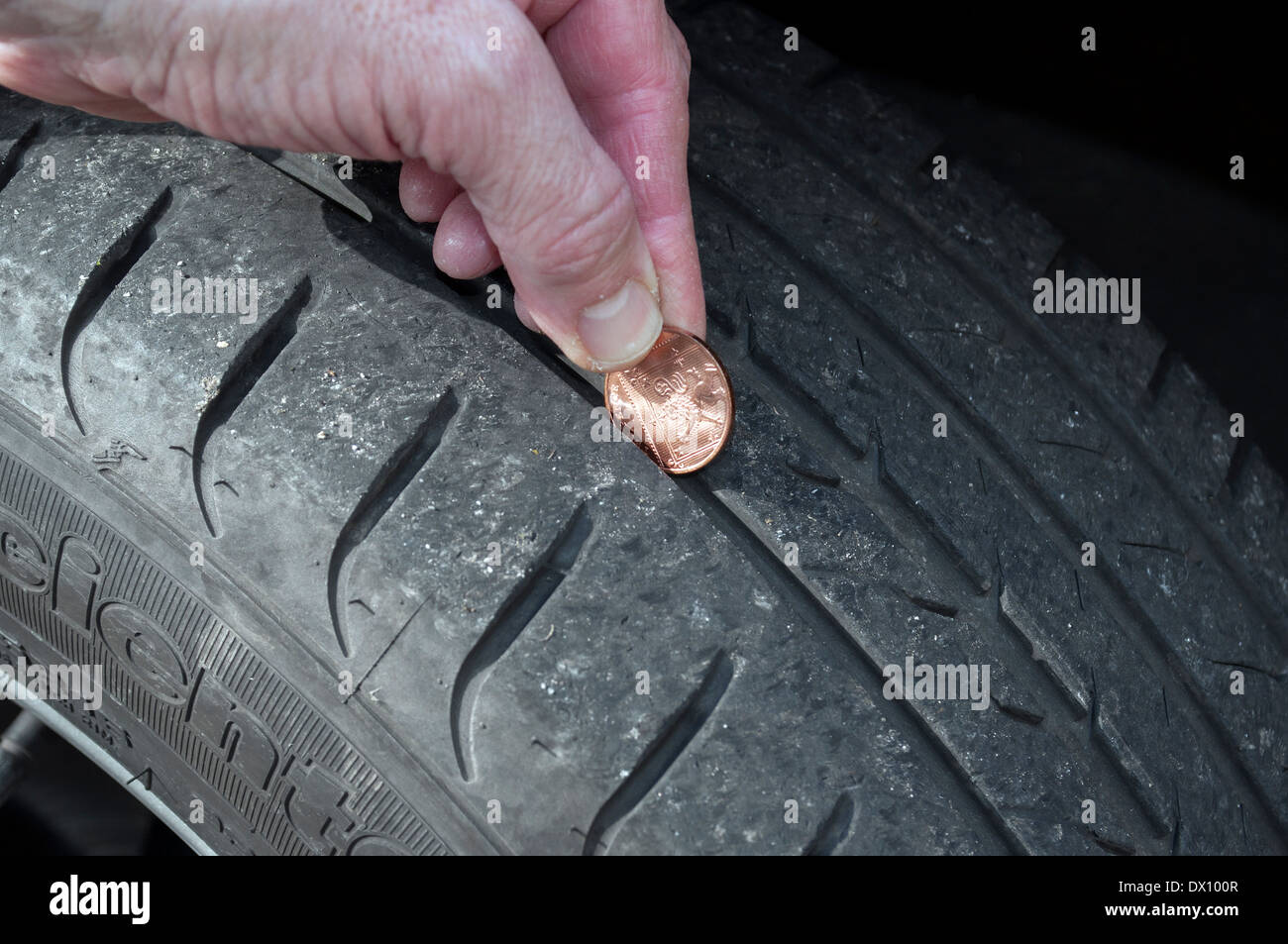 checking the tread depth on car tyre using a coin - Stock Image
