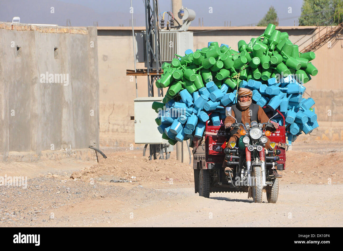 An Afghan man rides a motorized tricycle loaded down with plastic pitchers at the Shur Andam Industrial park November 7, 2012 in Kandahar City, Afghanistan. - Stock Image
