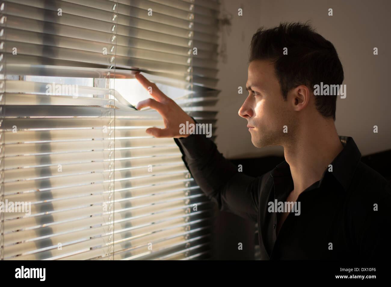 Profile of young man peeking through venetian blinds in a dark room - Stock Image