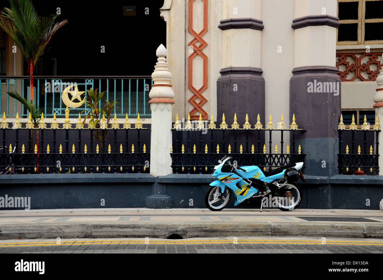 Blue yellow sporty motorcycle parked on pavement outside Sultan Mosque Kampong Glam Singapore Stock Photo