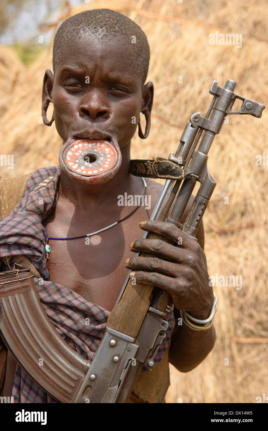 Mursi woman with lip plate and Kalashnikov in the Lower Omo Valley of Ethiopia. - Stock Image
