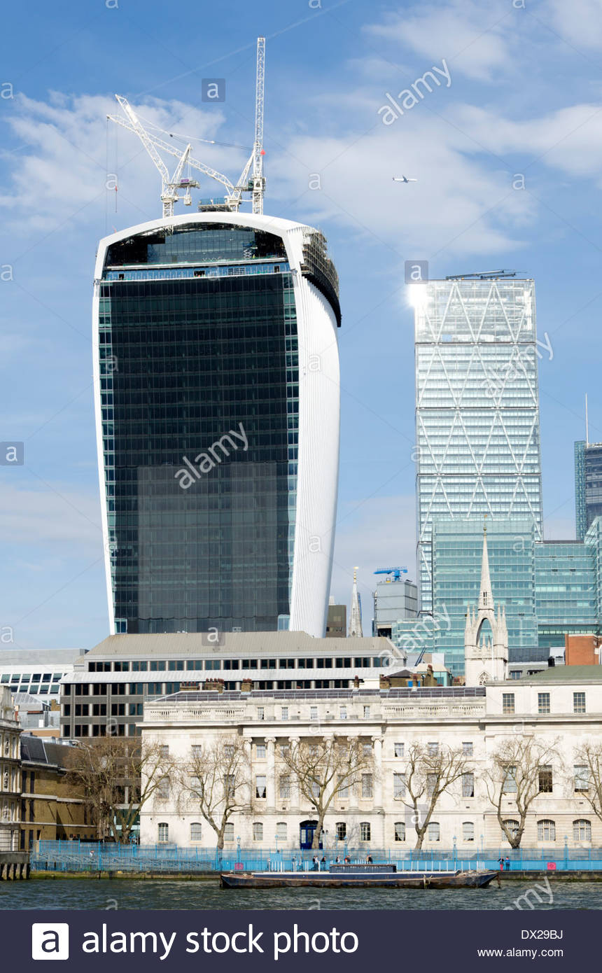 Light reflects from 'The Cheesegrater', while the 'Walkie Talkie' is shrouded to reduce the glare. - Stock Image