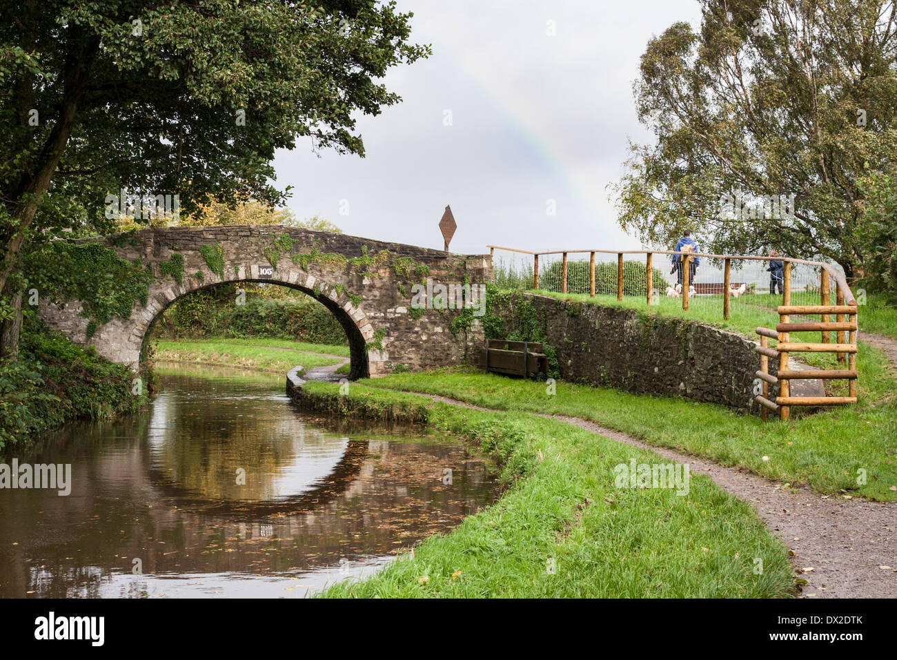 Dog walkers cross over the Sand Bridge No 105 on the Monmouthshire and Brecon Canal, Wales, GB, UK. Stock Photo
