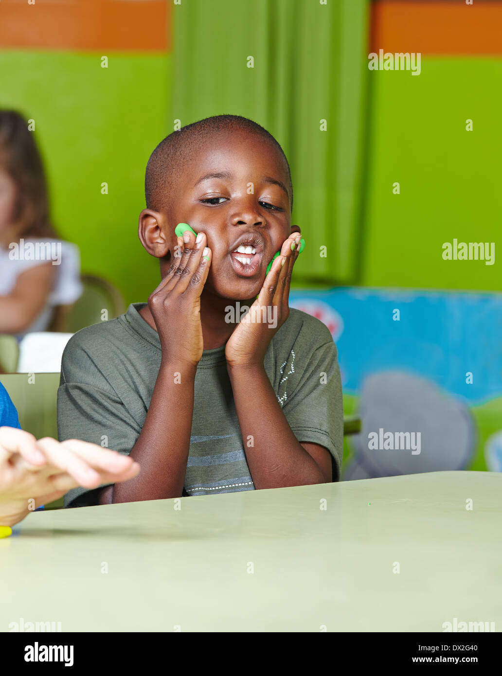 Silly african child making nonsense with dough in a kindergarten - Stock Image