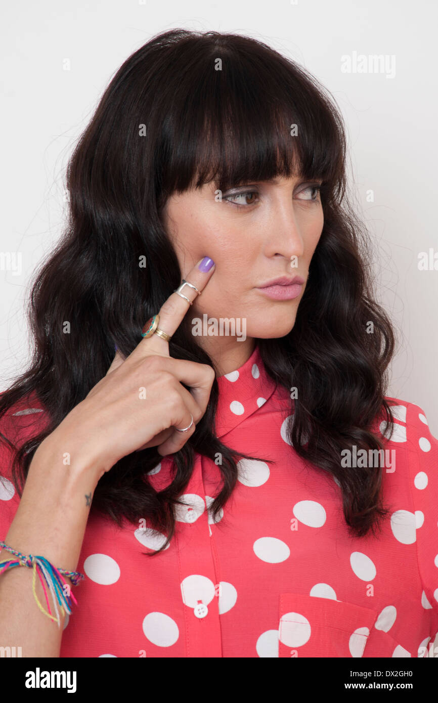 dark haired woman thinking finger cheek - Stock Image