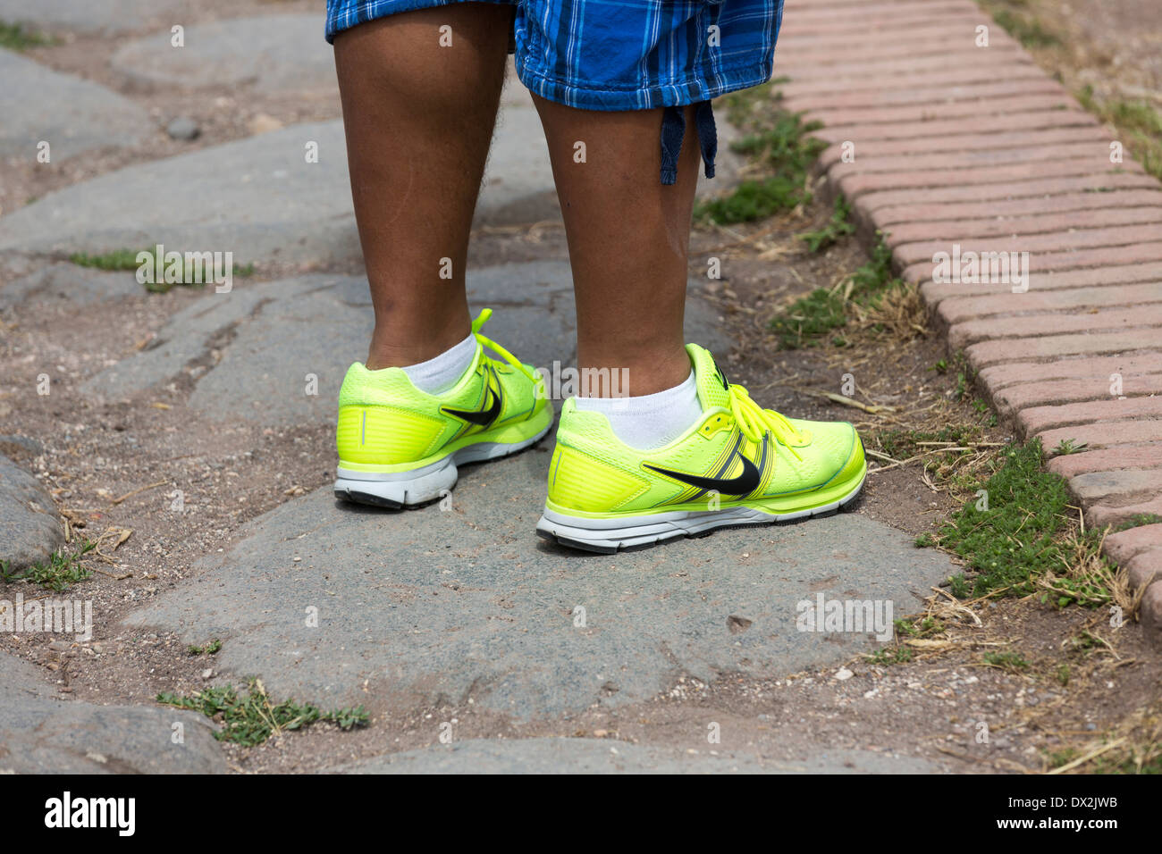 boy wearing fluorescent Nike shoes, Roman forum, Rome, Italy Stock Photo