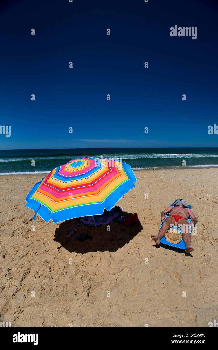 man sun baking beach umbrella rainbow Stock Photo
