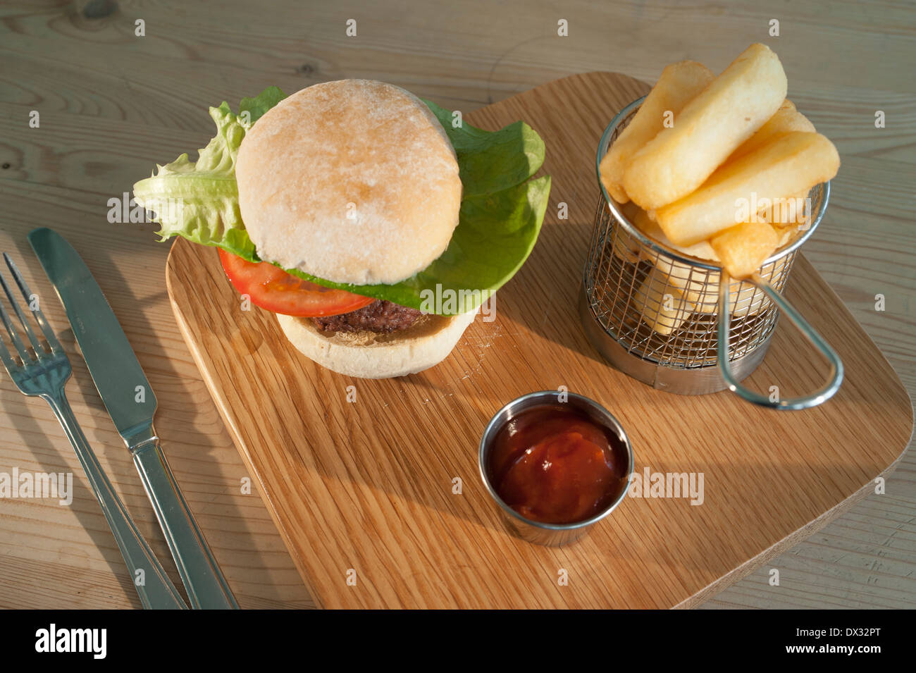 Burger with a salad garnish in a white bread bun with a side order of French fries and tomato ketchup served on Stock Photo