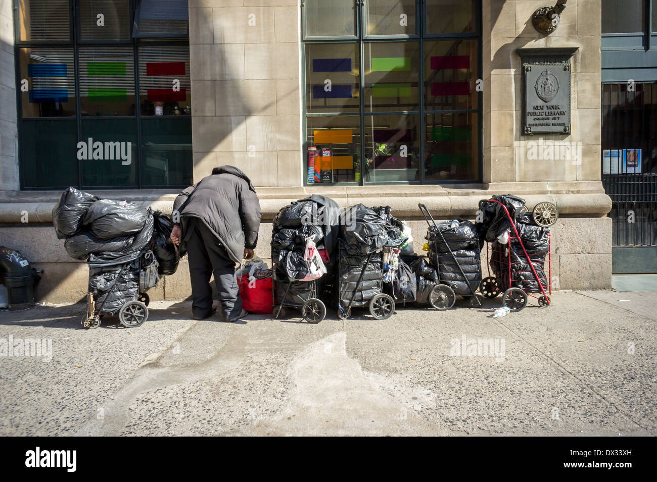 A hoarder with his possessions in front of the New York Public Library in the Chelsea neighborhood of New York - Stock Image