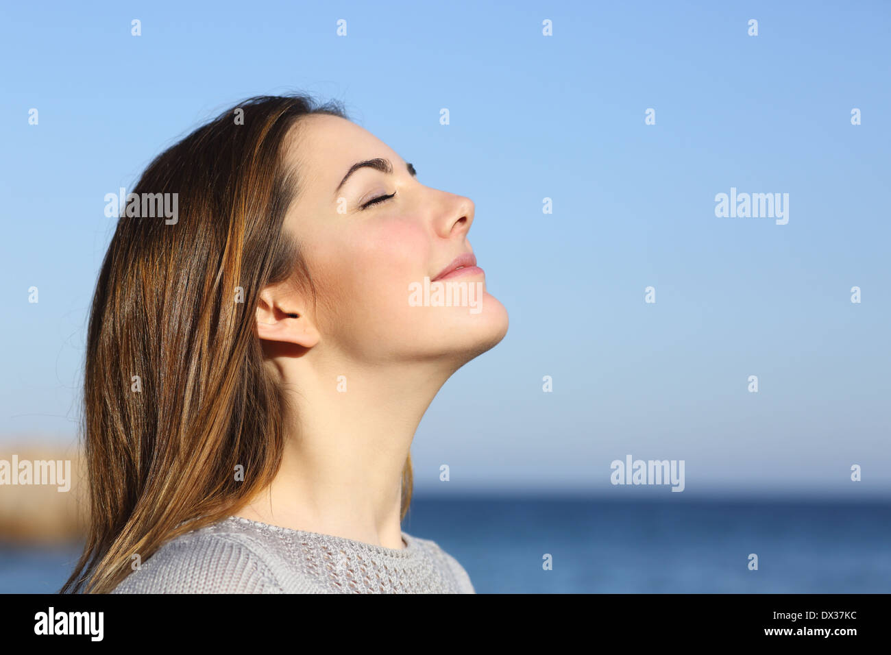 Woman profile portrait breathing deep fresh air on the beach with the ocean in the background - Stock Image