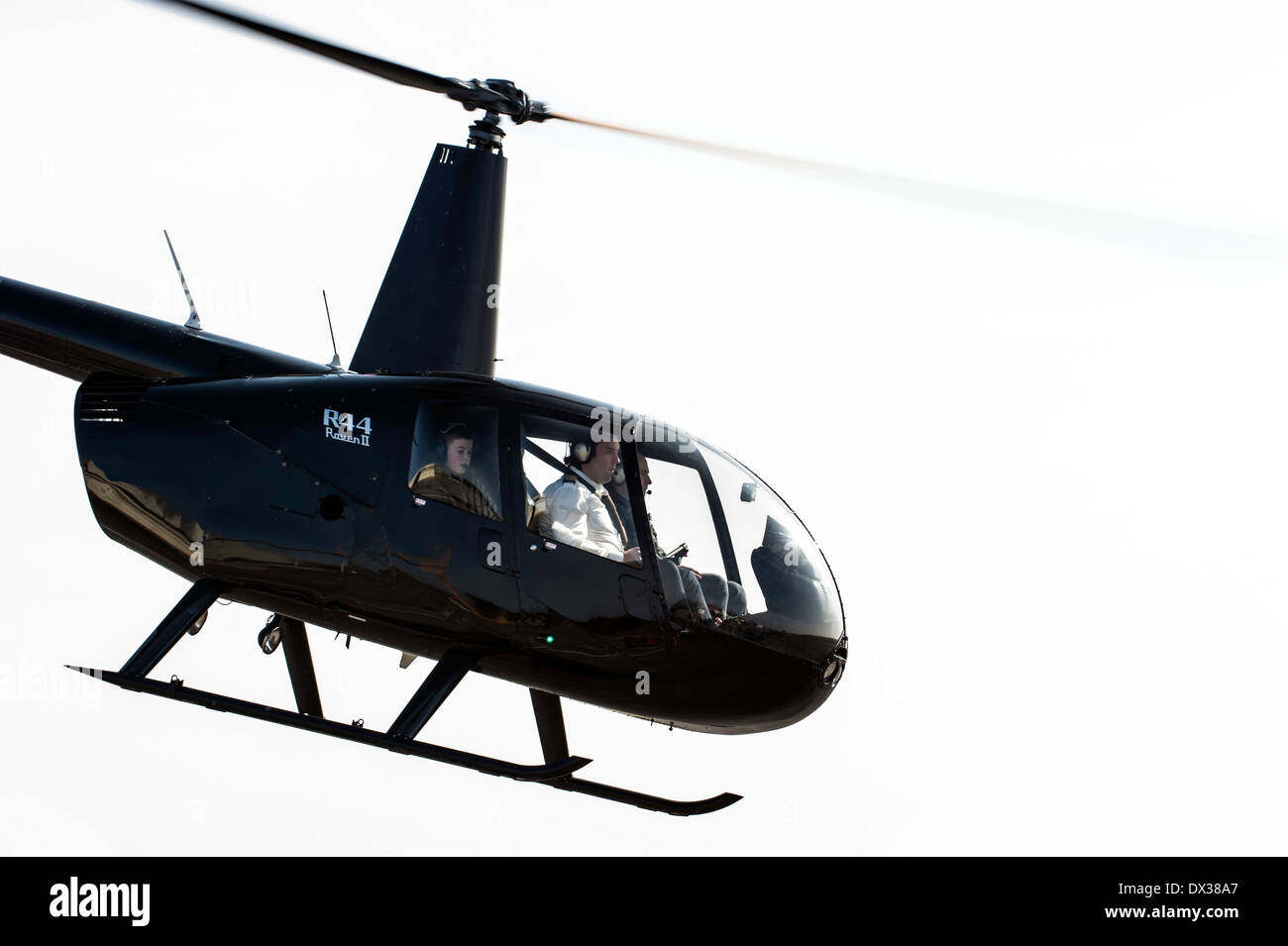 Robinson R44 Raven II, four-seat single-engined helicopter with semi-rigid two-bladed main rotor and skid landing gear in flight - Stock Image