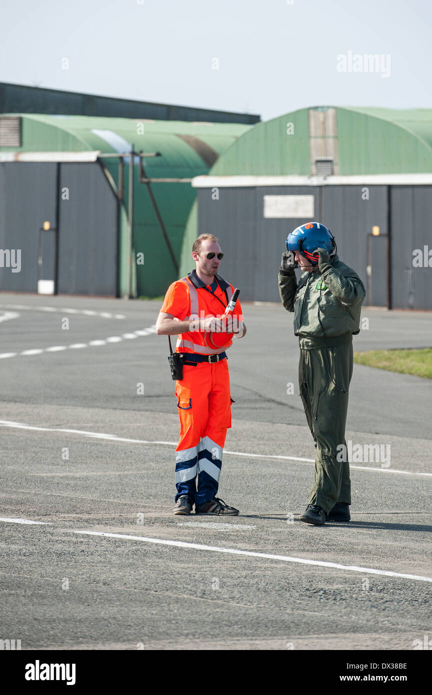 Marshaller and military helicopter pilot at airport - Stock Image