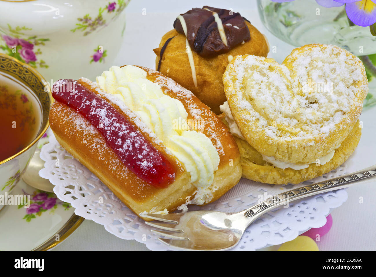 Traditional afternoon tea with cream cakes and vintage tea set. - Stock Image