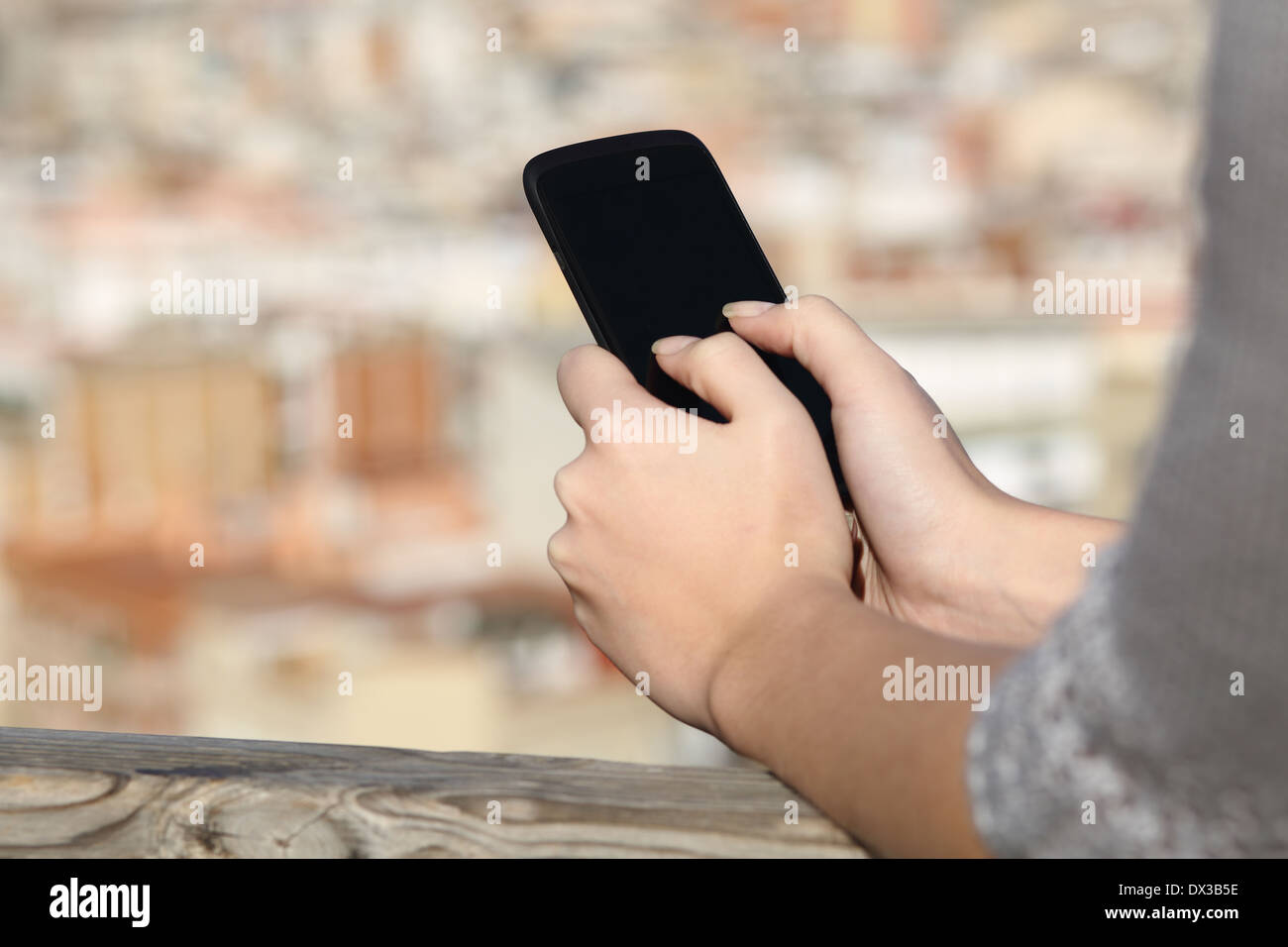 Woman hands texting on a smart phone screen with an urban background - Stock Image