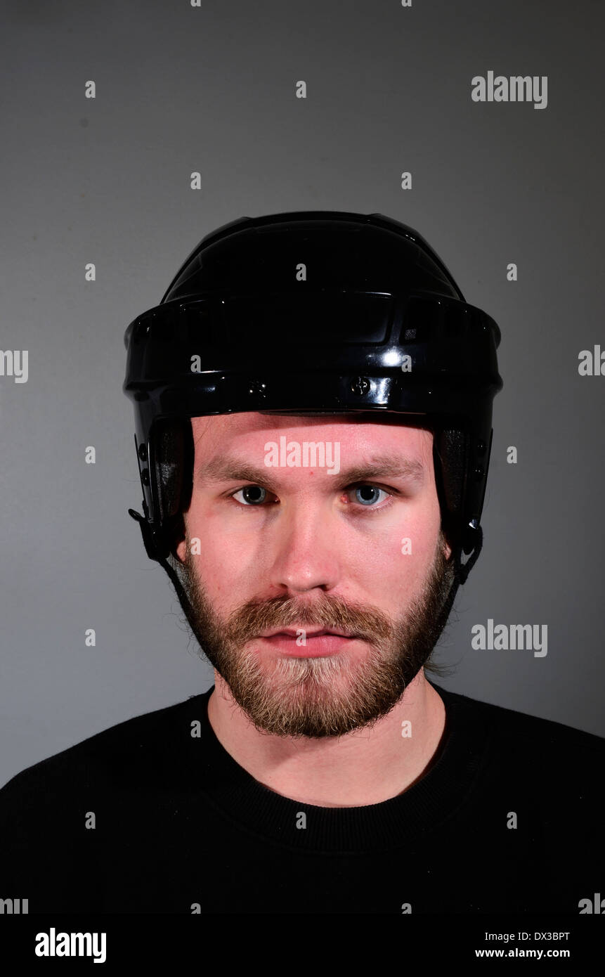 portrait of young man with beard and mustache in hockey helmet - Stock Image