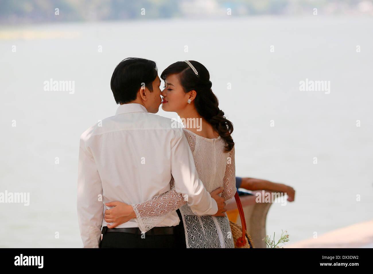 A Vietnamese couple having their engagement photographs taken by the Hoan Kiem Lake in Hanoi - Stock Image
