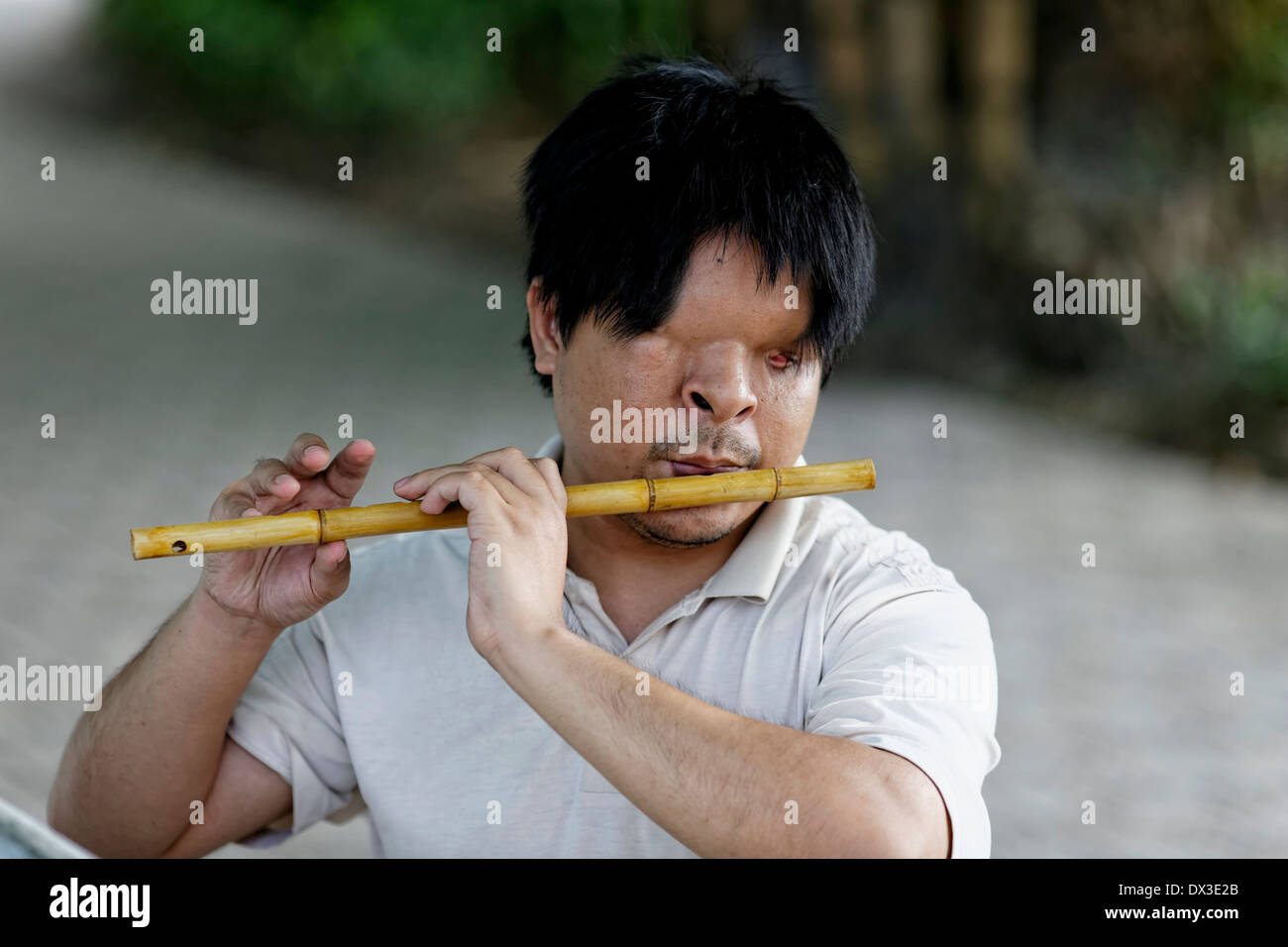 A blind musician plays a bamboo flute at the entrance to the Ngoc Son Temple, Hanoi, Vietnam,  South East Asia - Stock Image