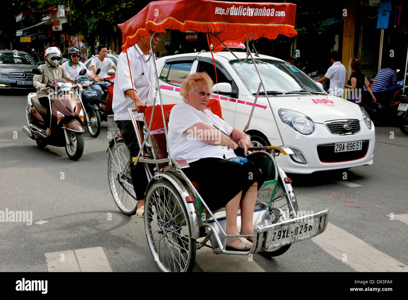 A woman tourist being given a tour of the old quarter on a cycle. Hanoi, Vietnam, Southeast Asia - Stock Image