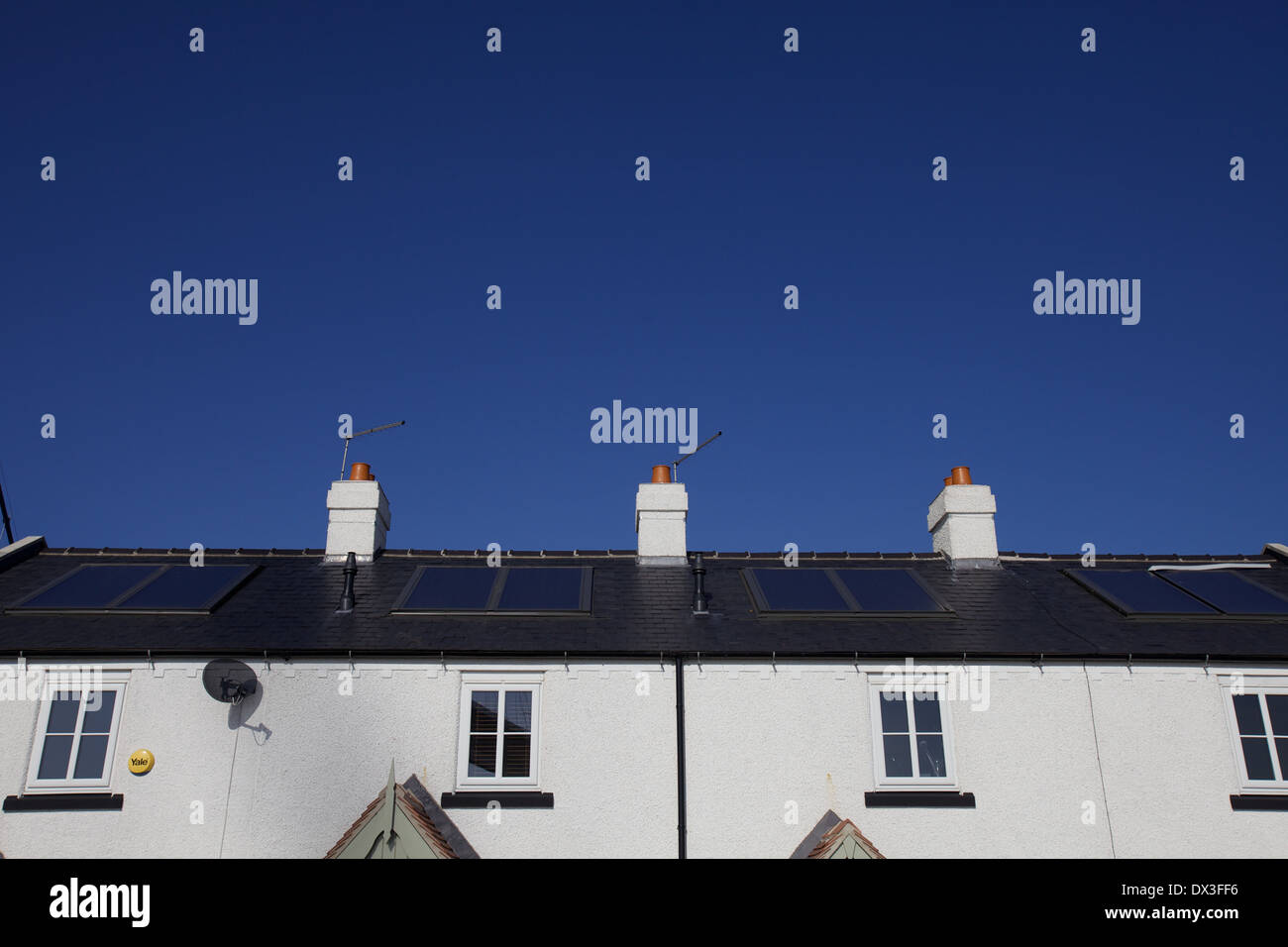 solar panels on a row of terraced houses - Stock Image