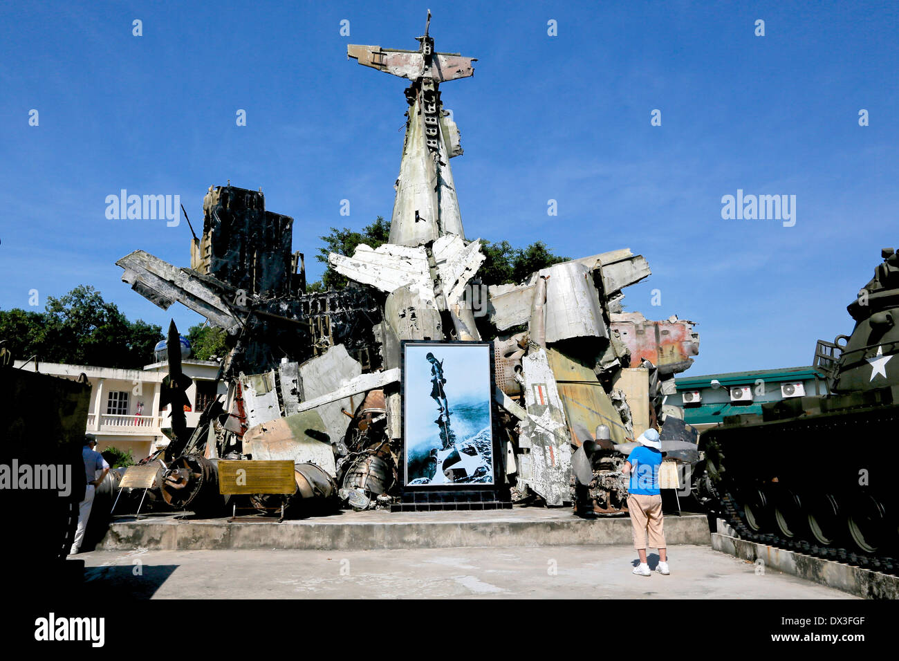 A Tourist looks at the wreckage of captured American planes at the Vietnam military history Museum, Vietnam, South East Asia - Stock Image