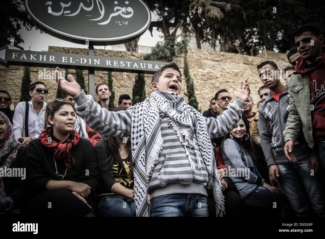 Ramallah, Palestinian Territories. 17th Mar, 2014. Palestinian Boy singing before being let inside of the Grand Stock Photo