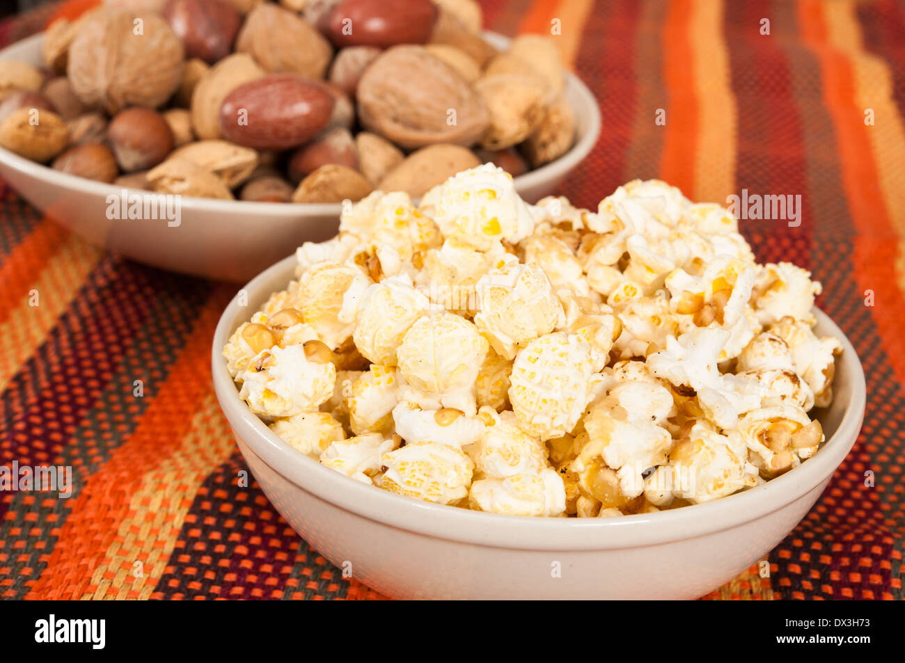 Dishes of mixed nuts and kettle popcorns - Stock Image