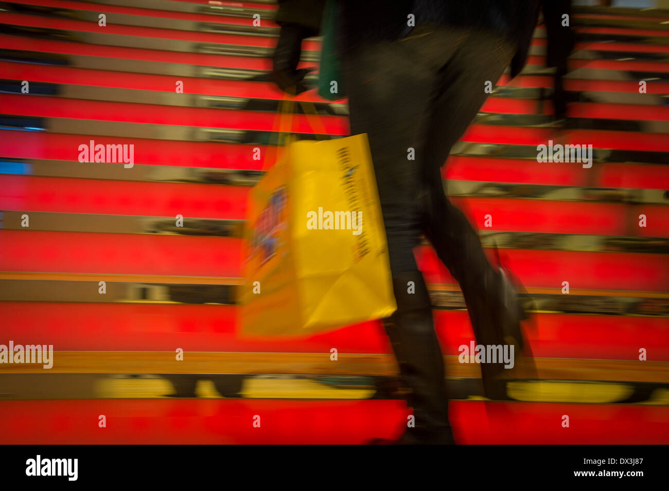 Woman Walking Up Red Steps Shopping In Mall - Stock Image