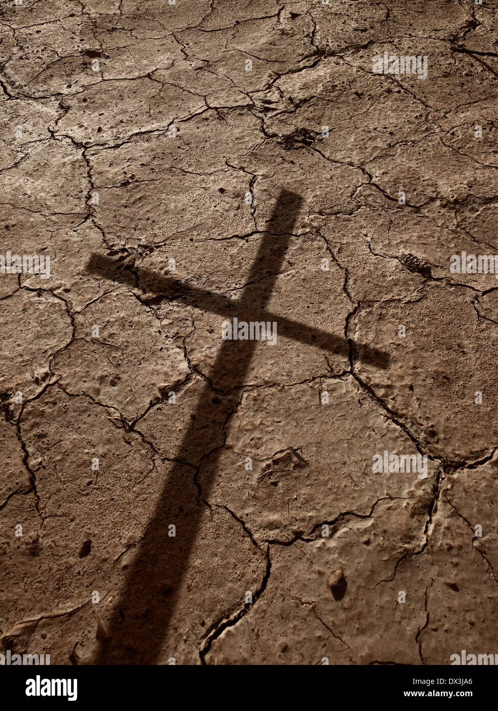 Shadow Of Cross On Dried Earth - Stock Image