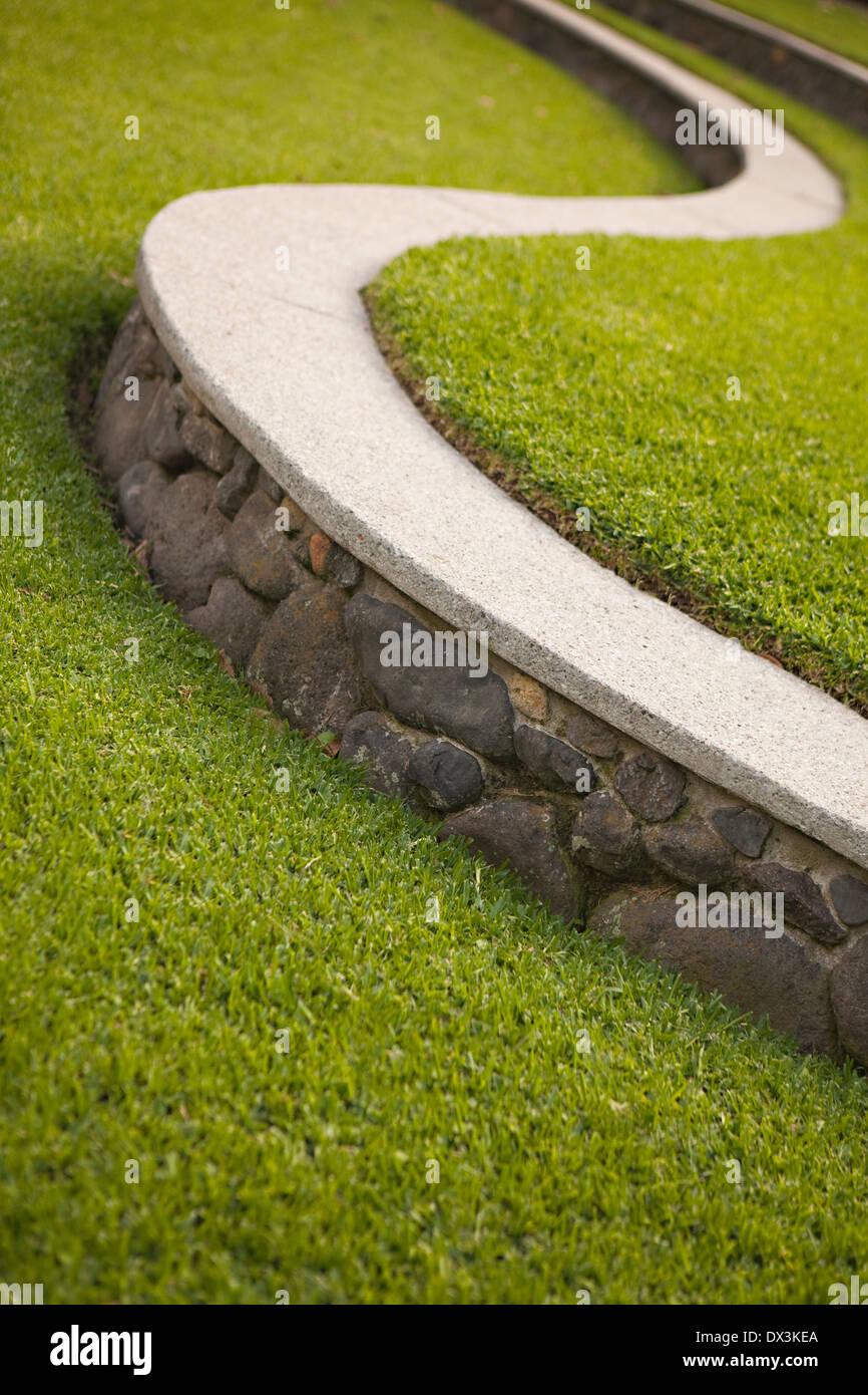 S-shaped ledge along landscaped green grass, tilt - Stock Image