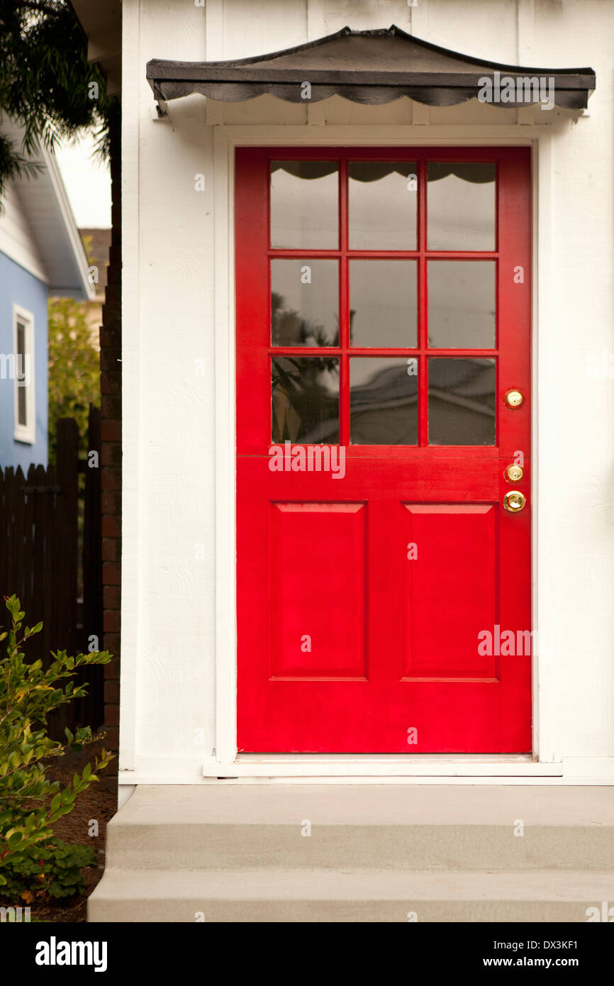 Red front door with black pagoda awning - Stock Image