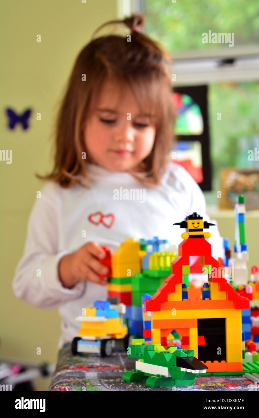 Child girl (age 3) plays in nursery room with Lego building bricks. - Stock Image