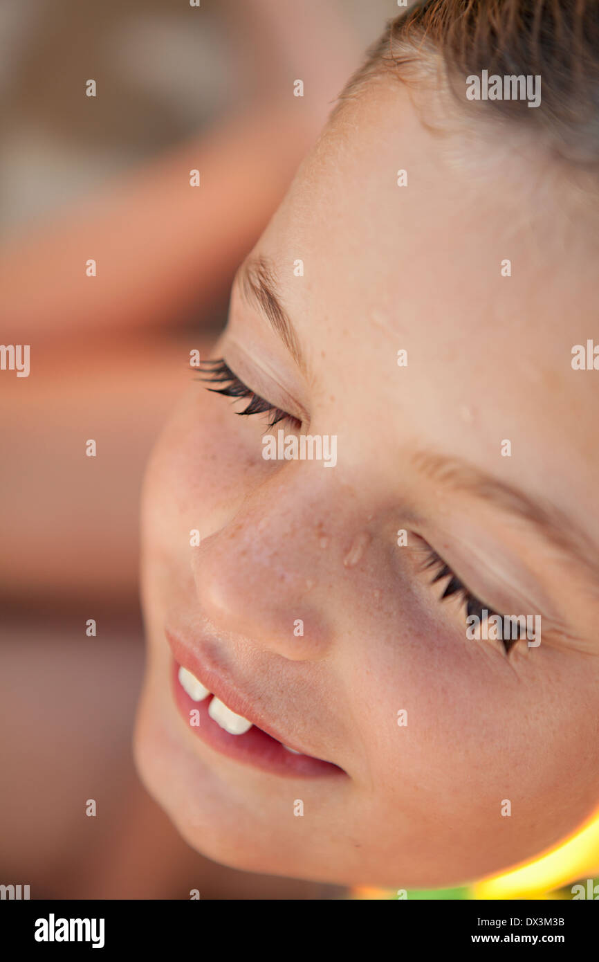 Girl with eyes closed and wet eyelashes after swimming, close up - Stock Image