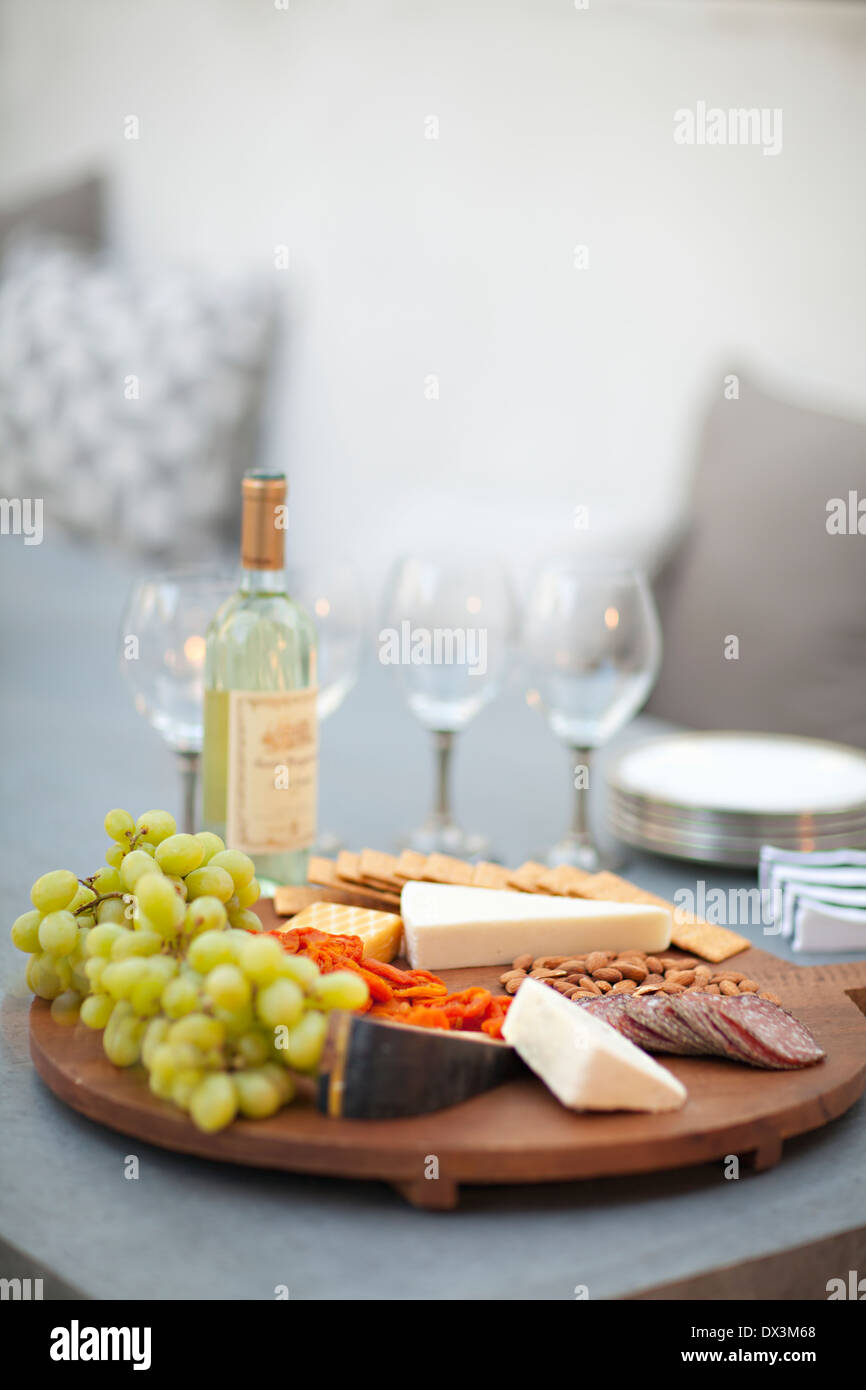 Cheese, crackers, nuts, grapes and salami on wooden cheeseboard next to white wine, tilt Stock Photo