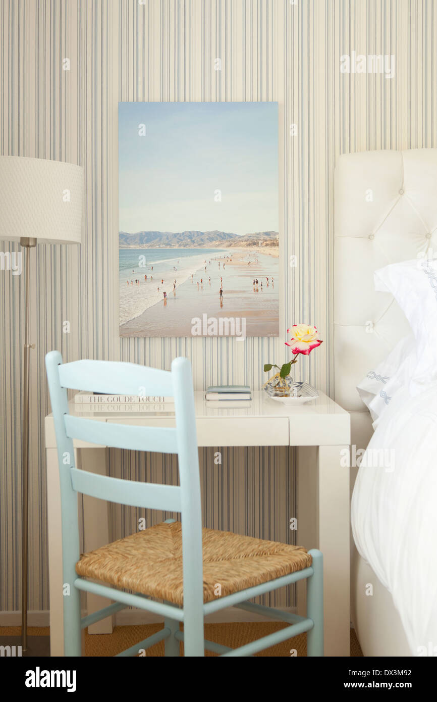 Beach painting above writing desk in blue and white bedroom - Stock Image