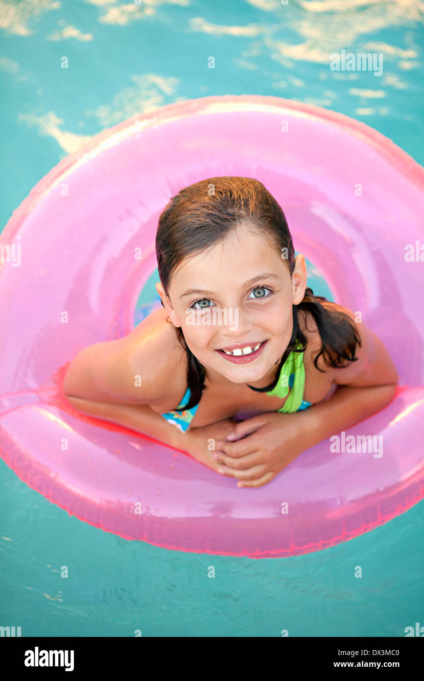 Smiling girl with wet hair inside of pink inflatable ring in swimming pool, portrait, high angle view - Stock Image