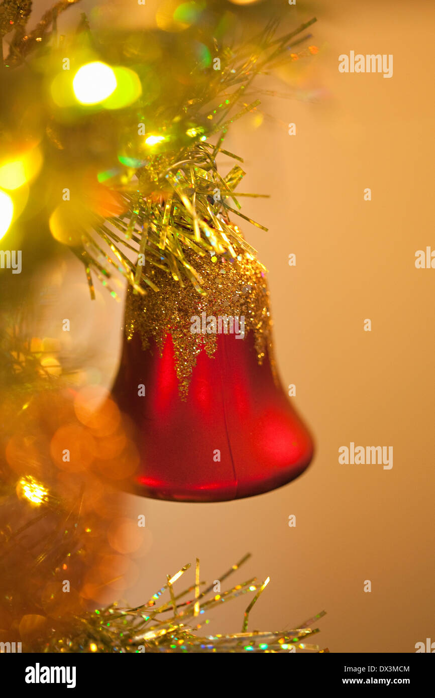 Red bell ornament hanging on illuminated Christmas tree, close up Stock Photo
